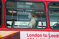 © Licensed to London News Pictures. 13/05/2020. London, UK.  A woman wearing a face covering on a London bus in north London. Under the new coronavirus lockdown rules issued by the government, members of the public are now being told to wear a face covering if possible when travelling on public transport. Photo credit: Dinendra Haria/LNP