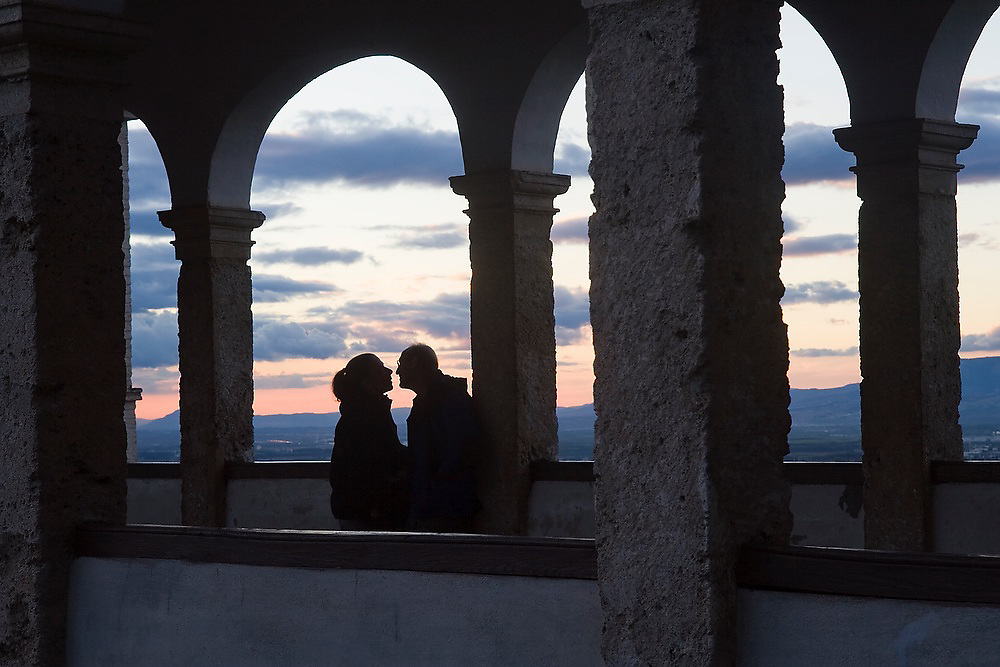 Liana and Parmenter Welty to kiss, silhouetted by the evening light under the arches of the Patio de la Acequia in the Generalife complex, La Alhambra, Granada, Andalusia, Spain.