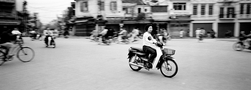 Young girl on motorbike driving by