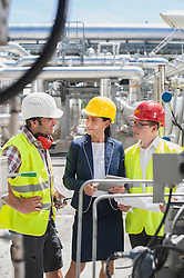 Engineer with his colleagues in meeting with digital tablet at geothermal power station, Bavaria, Germany