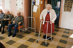 Elderly woman walking in residential home using zimmer frame,