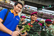 27 MAY 2014 - BANGKOK, THAILAND: A Thai man brings roses to soldiers stationed at Victory Monument in Bangkok. It's not unusual for supporters of the military to bring flowers and drinks to soldiers stationed on the street. Several hundred people protested against the coup in Bangkok at Victory Monument. It was the fourth straight day of pro-democracy rallies in the Thai capital as the army continued to tighten its grip on Thai life. The protest Tuesday was the smallest so far.     PHOTO BY JACK KURTZ