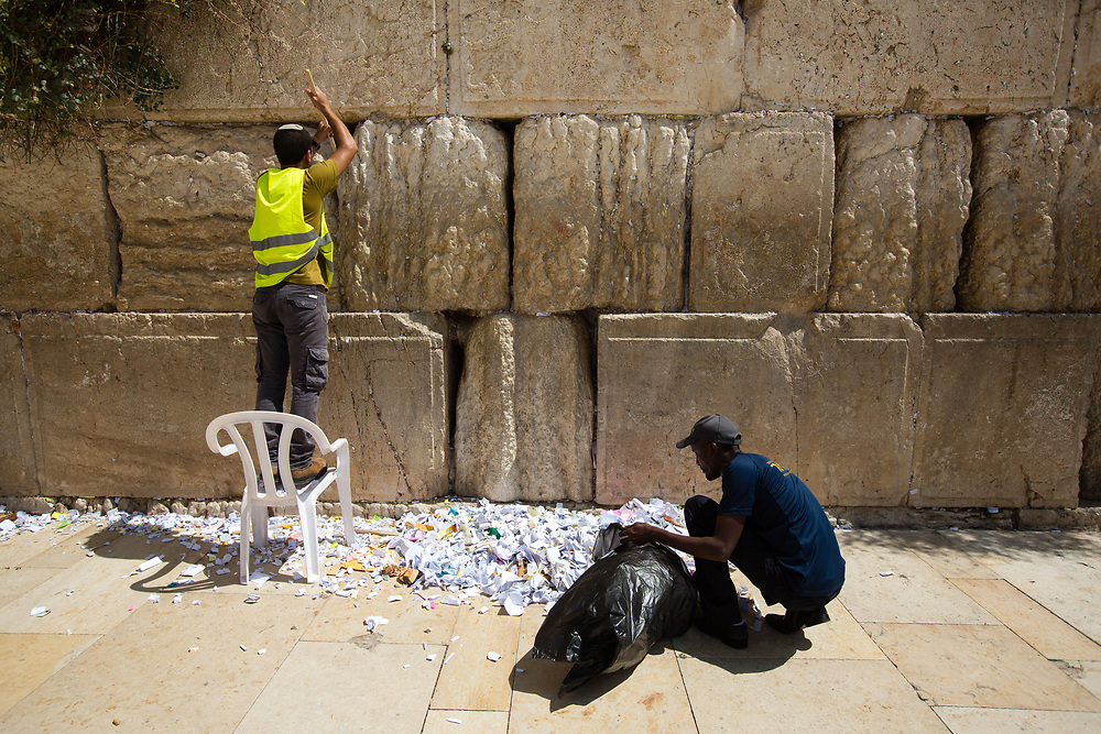 Workers remove notes containing prayers and messages which were left by visitors, from the cracks between the stones of the Western Wall, Judaism's holiest prayer site, in the Old City of Jerusalem, Israel, on September 17, 2017. The clean-up which takes place ahead of the upcoming Jewish New Year Holiday, clears the wall's crevices and frees up space for more notes that people of all faiths slip between its stones, believing that requests deposited at the site are more likely to be heard by God.