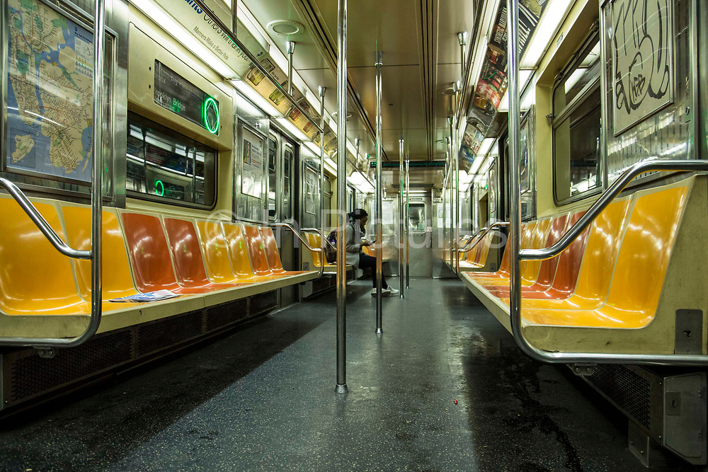 A woman sits alone and checks her phone in a subway carriage travelling to Brooklyn Bridge, Manhattan, New York City, New York, United States of America.