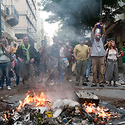 Protestors in Mitropoleos Str are watching the police operations in Syntagma Sq. The fire was lit to protect people from tears gas that was thrown extensively by riot police in Athens , June 29, 2011