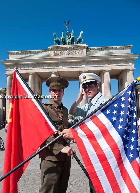 Actors in Soviet and American uniforms posing in-front of Brandenburg Gate in Berlin Germany
