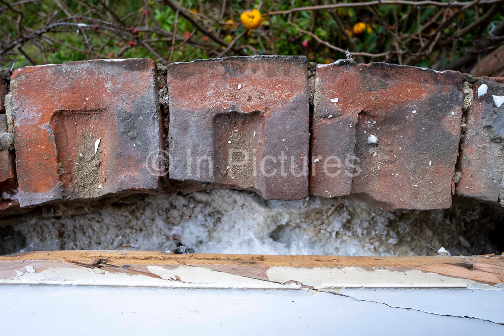 Cavity Wall insulation between the external brickwork and internal windowsill of a 1930's house on the 23rd of January 2020 in Folkestone, Kent, United Kingdom. Cavity Wall insulation is a process used to retrospectively fill the cavity of an external wall with a cotton type foam providing insulation and improving the heat retention of a property, offering savings on the cost of heating that property and saving energy.