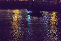 Victoria Embankment, London, January 20th 2017. Bomb disposal experts from the Royal Navy at Victoria Embankment to defuse and remove an unexploded bomb discovered,  between Hungerford Bridge and Westminster Bridge, near the Houses of Parliament, by engineers working in the River Thames. PICTURED: With a floatation device attached to the bomb, it is towed down the river behind a police RIB.