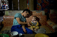 A Hmong man shows his son an image from his phone while sitting together on a worn couch in their home in Lao Chai, Lao Cai Province, Vietnam, Southeast Asia