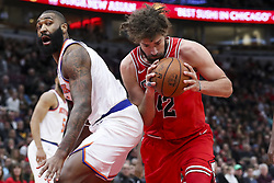 December 27, 2017 - Chicago, IL, USA - The New York Knicks' Kyle O'Quinn, left, looks back at the Chicago Bulls' Robin Lopez (42) while the drives to the basket during the first half at the United Center in Chicago on Wednesday, Dec. 27, 2017. (Credit Image: © Armando L. Sanchez/TNS via ZUMA Wire)