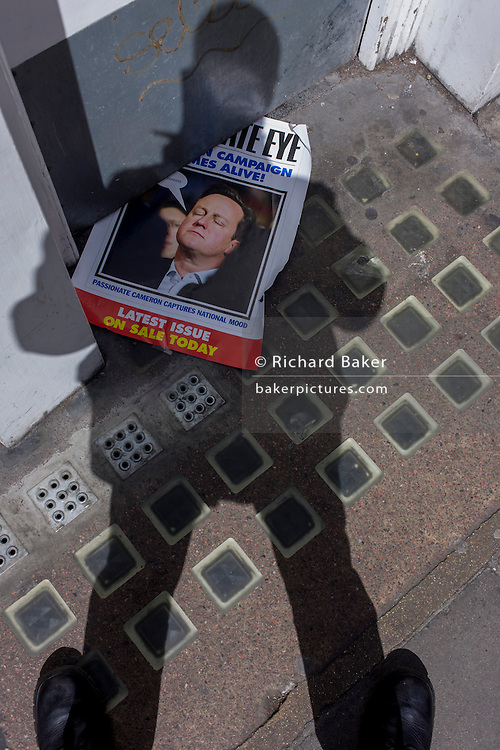 Prime Minister David Cameron appearing on the cover of satirical magazine Private Eye, on the pavement in Soho, central London.