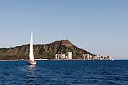 A sailboat sails by Diamond Head Crater in Waikiki.