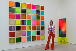 """© Licensed to London News Pictures. 21/10/2020. LONDON, UK. British artist Nat Bowen poses with her work """"Fragments"""", 2020. Bowen uses the study of Chromology, the psychology behind colour, as a way to communicate non verbally through her work. Preview of STARTnet Art Fair at the Saatchi Gallery in Chelsea.  The contemporary art fair showcases local London, as well as international, galleries and individual artists from all over the world.  The fair runs 21 to 25 October with Covid-19 protocols in place for visitors.   Photo credit: Stephen Chung/LNP"""