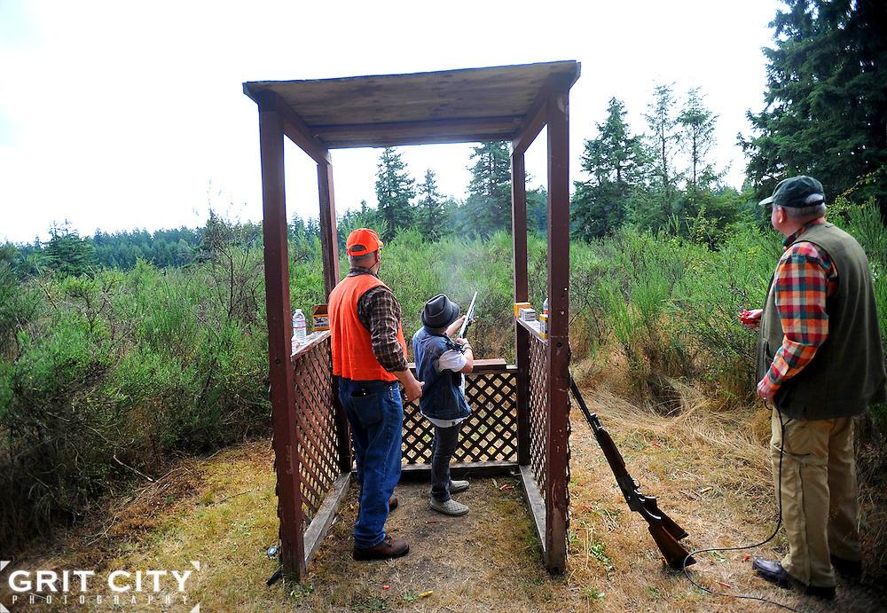 Ken Welsh, left, Western Washington Pheasant Releasers volunteer, and Paul Hunter, right, watch Sage Burgamy, 9, fire a shotgun Aug. 13 during the Youth Shotgun Shoot at the Lewis Main Skeet Range.