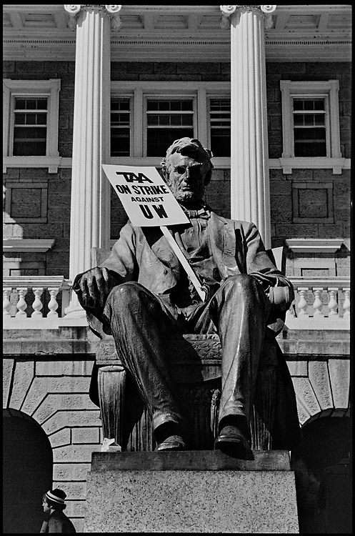 """Madison, WI - March 1970. On March 15, 1970, the University of Wisconsin - Madison Teaching Assistants' Association voted to strike, and the campus was filled with picket lines as well as demonstrations of related and other issues. The strike lasted until early April, when the Association and University came to an agreement. The statue of Abraham Lincoln in front of Bascom Hall with a sign that reads """"TAA on strike against UW."""""""