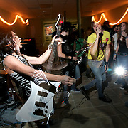 """Robert Galvan, left, 15, plays the bass guitar while Basilio Villareal, right, screams into the microphone as """"The Emergency Numbers"""" play in front of a small teenage crowd at Friday Night Live in downtown McAllen.<br /> Nathan Lambrecht/The Monitor"""