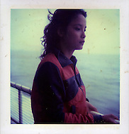 Portrait of a Vietnamese woman contemplatively watching the sea while she stands on the deck of a boat holding the railing, Halong Bay, Quang Ninh Province, Vietnam, Southeast Asia