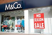 Mid season sale sign clothes shop window M&Co clothes shop