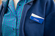 Model released teenage girl in uniform for her job in a Co-operative shop, UK wearing a badge saying 'In Training'
