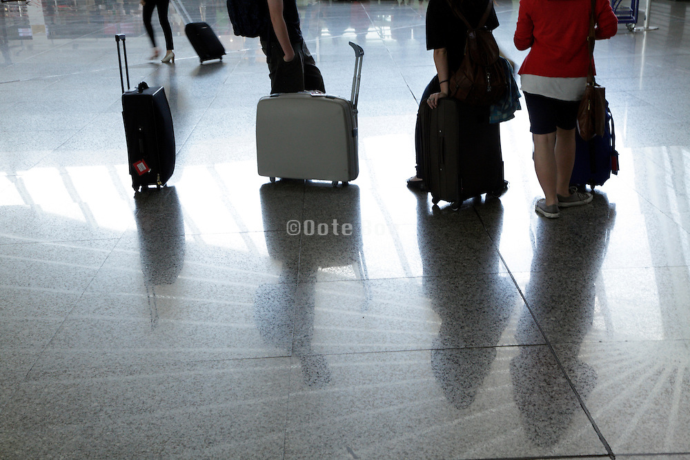 airport terminal with young adults standing and waiting