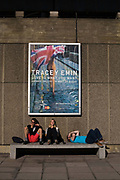 Three young people relax underneath a poster advertising a show by the artist, Tracy Emin by the Nationa Film Theatre on the South Bank, London, UK