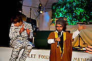 Glastonbury Festival 2014.<br /> Self branded 'Migga' (midget) Imaan Hadchiti  doing stand up comedy in the heaven tent<br /> Shangri-La is the after-hours epicentre of Glastonbury Festival, a largely indescribable, ephemeral and interactive world that really comes to life after dark.<br /> Unique among festivals, Shangri-la has a central narrative that pins it all together,  it evolves year by year (a bit like Star Wars). All contributors respond to this narrative, and add to it via their installations, venues and performances. When it all comes together on site the audience have a wholly immersive world to become lost in with a myriad of places to explore.<br /> Exploration and discovery is an important aspect of  Shangri-la. A maze of covered alleys is riddled with nano-venues, performers and installations, artworks and hidden doors.<br />  In 2014 Shangri-La explored the way we create heavens and hells for ourselves.