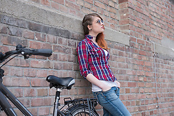 Young woman leaning on wall with bicycle, Munich, Bavaria, Germany
