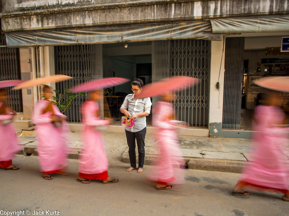 "26 APRIL 2014 - TACHILEIK, SHAN STATE, MYANMAR: Buddhist  nuns go out on their alms rounds in the morning in Tachileik, Shan State, Myanmar (Burma). There are about 75,000 Burmese women living as nuns, sometimes called ""Bhikkhuni"" although the term has fallen out of favor since Bhikkhuni are no longer ordained. Many of the women who become nuns to so to escape poverty or abuse.   PHOTO BY JACK KURTZ"