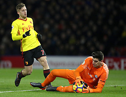 Watford's Gerard Deulofeu (left) has a shot on goal saved by Chelsea goalkeeper Thibaut Courtois during the Premier League match at Vicarage Road, Watford.