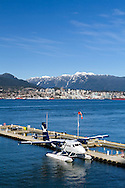 A West Coast Air Twin Otter (De Havilland Canada DHC-6-100 Twin Otter C-FGQH) at the Vancouver Harbour Water Airport (CXH). The City of North Vancouver and Mount Seymour are in the background. Photographed from the Vancouver Trade and Convention Center in Vancouver, British Columbia, Canada