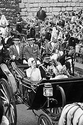 Queen Elizabeth II waves from the open carriage as she drives with Prince Philip, Duke of Edinburgh and Princess Anne past the King's Gate of Caernarfon Castle to the investiture of the Prince of Wales.