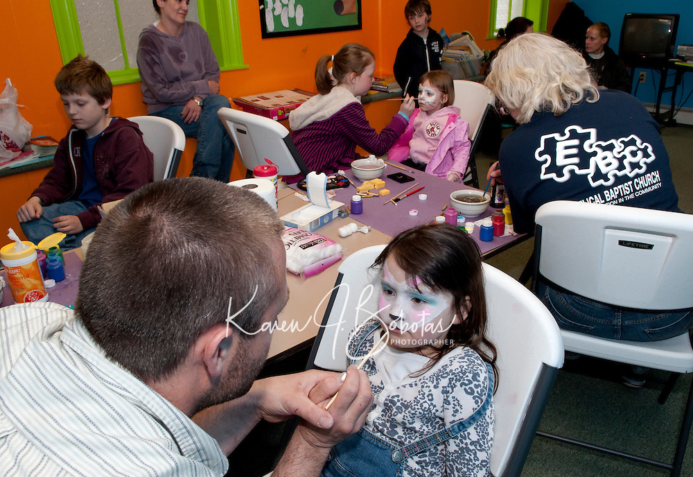 "Mr. Ashley Todd paints an ""eggstravagant"" bunny face on Jodi Chamberlain at the Evangelical Baptist Church following the Egg Hunt at Laconia Rotary Park Saturday afternoon. (Karen Bobotas/for the Laconia Daily Sun)"
