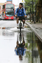 © Licensed to London News Pictures. 27/07/2019. London, UK. Manuel Usai.Lod rides a bicycle through a flood on Green Lanes in north London, caused by heavy overnight downpour. Photo credit: Dinendra Haria/LNP