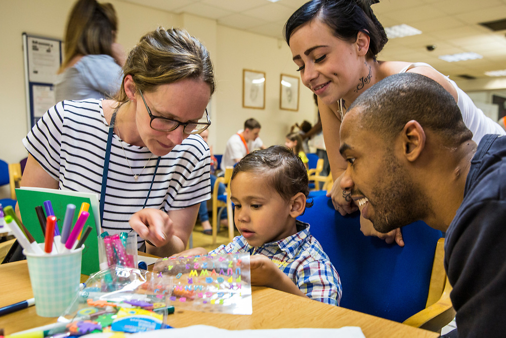 A PACT support worker chats to a family as they play with their kids during a family visit in HMP Brixton, South London on the 26th of July 2016, London United Kingdom. The Prisoner Advice & Care Trust (PACT) organise special family days that help the men inside the prison connect with and support their partners and children on the outside. (photo by Andy Aitchison)