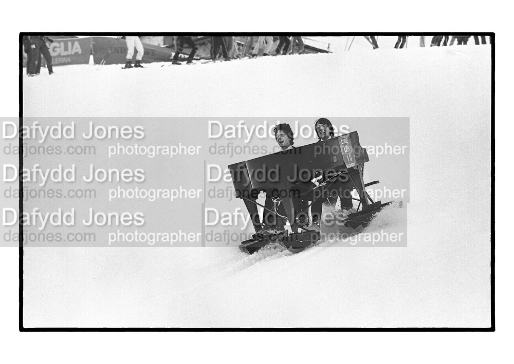 Hugo Spowers & Hubie Gibbs going down the slope on a piano during the Dangerous Sports Club Ski race. St. Moritz. 1983.