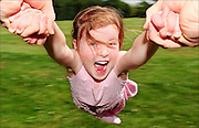 A young girl being happily swung around by her arms. The joy of childhood