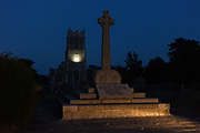 The sundial on the spire of Holy Trinity church  as car headlights illuminate the war memorial for both world wars, on 12th August 2020, in Loddon, Norfolk, England.