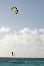 Caribbean, Netherlands Antilles, Bonaire.  Kite-surfer in mid-air above the Caribbean Sea.