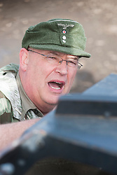A reenactor portraying German officer wearing an M43 ski cap (Einheitsfeldmütze) and splinter pattern camouflage smock speaks to an armored vehicle driver during preparation for a Battle reenactment on the Pickering Showground during the towns wartime weekend<br />