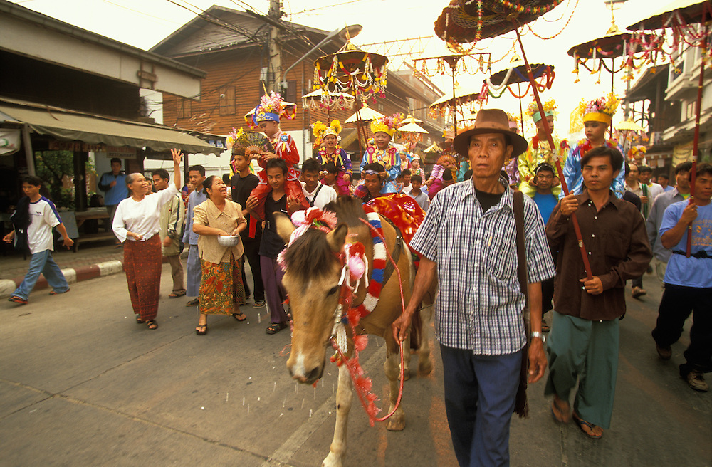 Procession with young boys dressed up as princes during Poy Sang Long, the yearly ordination of novice monks, Mae Hong Son, Thailand. April 2003. On the horse in front rides the invisible guardian spirit of the town.