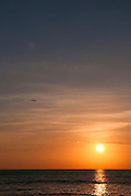 The sun at sunset with an airplane departing.