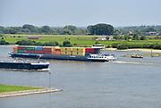 Nederland, Varik, 9-6-2018Een binnenvaartschip vaart over de Waal beladen met containers richting Duitsland .In dit deel van de Waal zijn de kribben verlaagd of vervangen door langsliggende dammen om de waterafvoer te verbeteren . Het fietsveer, voetgangerspontje, vaart aan de overkantFoto: Flip Franssen