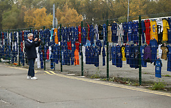 A supporter takes a photo of shirt tributes, left for the victims of the Helicopter crash, which have been re-located to a new memorial site nearer to the crash site at the King Power Stadium, Leicester.