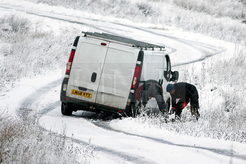 © Licensed to London News Pictures. 14/01/2016. Ribblehead UK. Two men attempt to recover their van after it slipped of the road in snow on the Newby Head Pass in the Yorkshire Dales Photo credit: Andrew McCaren/LNP