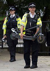 © Licensed to London News Pictures. 20/08/2021. London, UK. A police officer carrying an e-scooter which was confiscated during a routine operation on the Harrow Road in Maida Vale, north west London. The use of privately owned e-scooters remains illegal except for on private land. A number of rental schemes are currently being trialed across the UK. Photo credit: Ben Cawthra/LNP