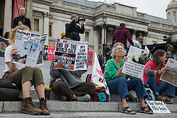 London, UK. 23rd August, 2021. Environmental activists from Extinction Rebellion read spoof newspapers bearing climate-based headlines in Trafalgar Square during the first day of Impossible Rebellion protests. Extinction Rebellion are calling on the UK government to cease all new fossil fuel investment with immediate effect. Credit: Mark Kerrison/Alamy Live News