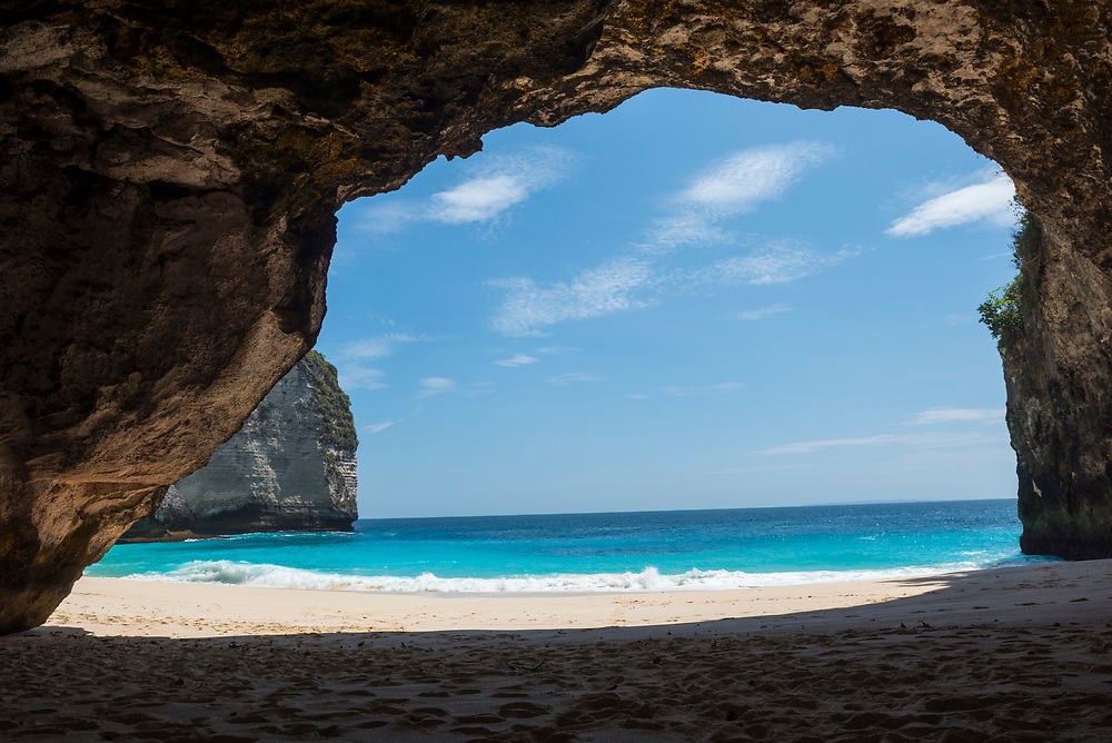 Nusa Penida, Indonesia - October 3, 2017: View of the beach and sea from a cave at Kelingking Beach on the tropical Indonesian island of Nusa Penida.