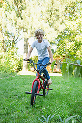 Young boy cycling in the garden