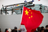 Members of the British Chinese community wait to board the Chinese Naval assault ship Chang Bai Shan at Portsmouth Royal Navy Base today. The ship is involved in the first visit by the Chinese Navy to the UK since 2007 and the largest ever. She is accompanied by the frigate Yun Cheng and the replenishment ship Chaohu. The ships arrived in Portsmouth 24 hours early due to the expected bad weather. The Royal Navy statement stated that the five day formal visit is aimed at enhancing military understanding between the UK and China. Picture date Monday 12th January, 2015.<br /> Picture by Christopher Ison. Contact +447544 044177 chris@christopherison.com