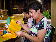25 AUGUST 2018 - GEORGE TOWN, PENANG, MALAYSIA: Woman in Yap Kongsi Temple make ghost money on Ghost Day, the full moon day (or night) that falls in the middle of Hungry Ghost month. The Ghost Festival, also known as the Hungry Ghost Festival is a traditional Taoist and Buddhist festival held in Chinese communities throughout Asia. Ghost Day, is on the 15th night of the seventh month (25 August in 2018). During Ghost Festival, the deceased are believed to visit the living. In many Chinese communities, there are Chinese operas and puppet shows and elaborate banquets are staged to appease the ghosts.       PHOTO BY JACK KURTZ